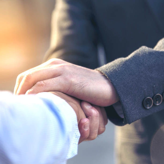 Two men in suits shaking hands, focus on just hands